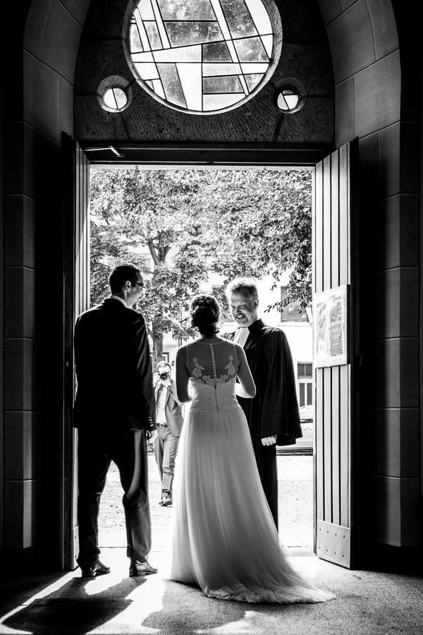 in der Kirchentür stehen Braut und Bräutigam und sind von hinten zu sehen