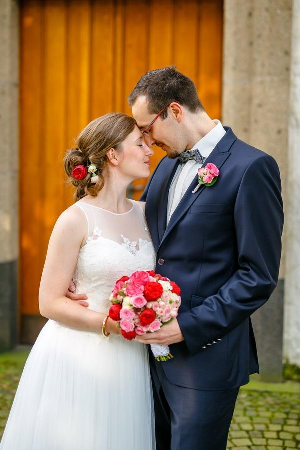 Braut und Bräutigam Stirn an Stirn vor der Kirchentür