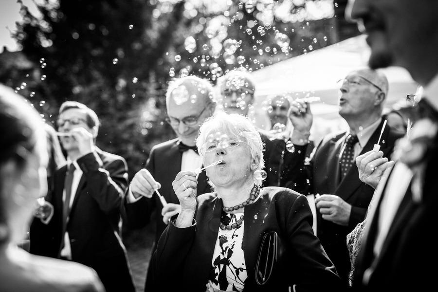 die Brautmutter bläst Seifenblasen vor der Kirche