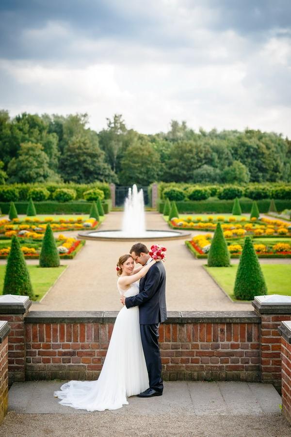 das Brautpaar steht auf einem Mauervorsprung vor einem Springbrunnen