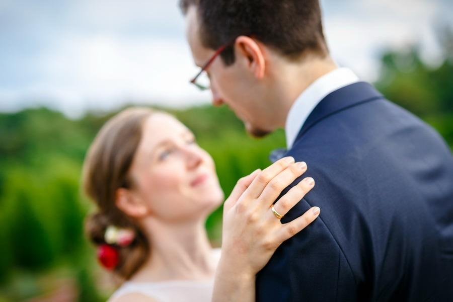 Braut und Bräutigam unscharf im Hintergrund, der Ehering ist im Fokus.
