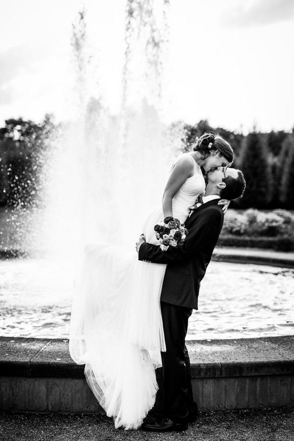 Braut und Bräutigam küssen sich vor einem Springbrunnen