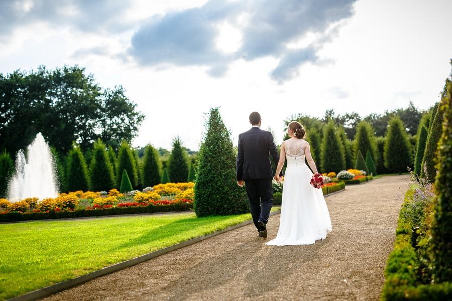 Braut und Bräutigam spazoeren durch einen bunten Garten