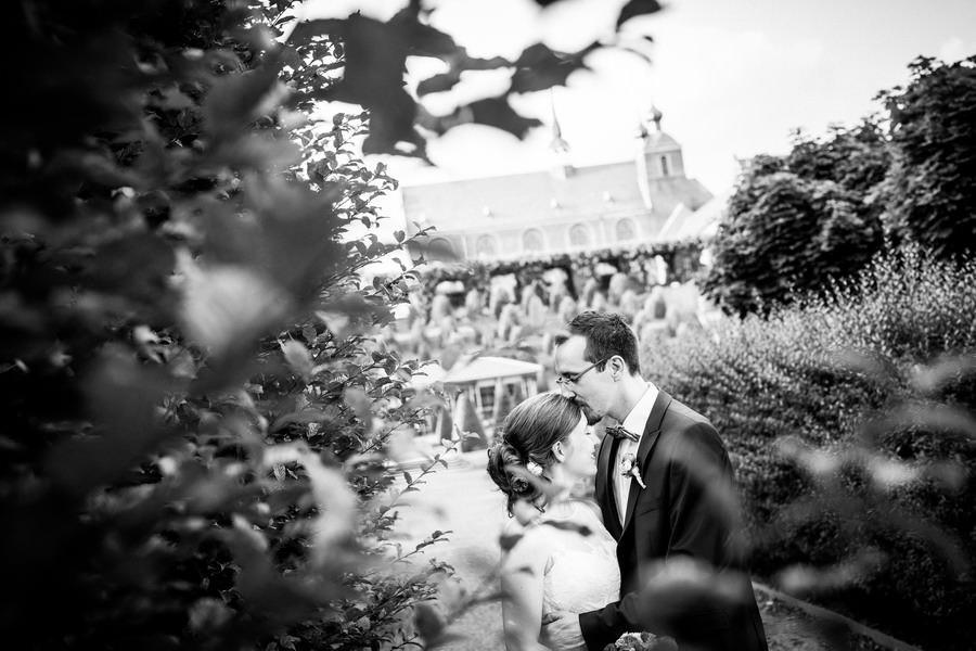 ein Brautpaar steht vor der Abtei Kamp-Lintfort, der Bräutigam küsst seiner Braut auf die Stirn