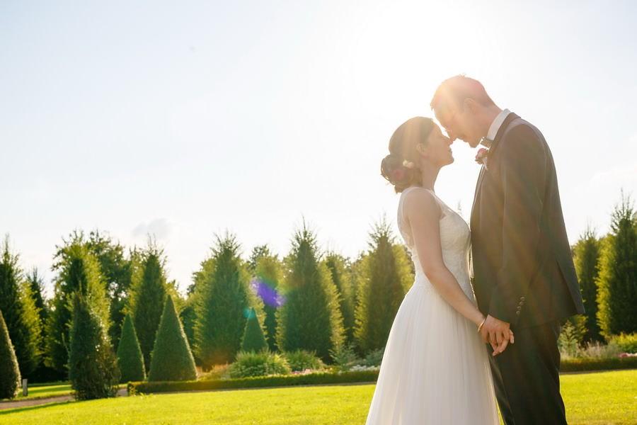 EIn Brautpaar steht sich Stirn an Stirn gegenüber, Sonnenstrahlen scheinen auf sie