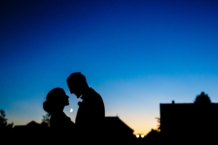 Die Silhouetten eines Brautpaares vor dunkelblauem HImmel, der Mond scheint