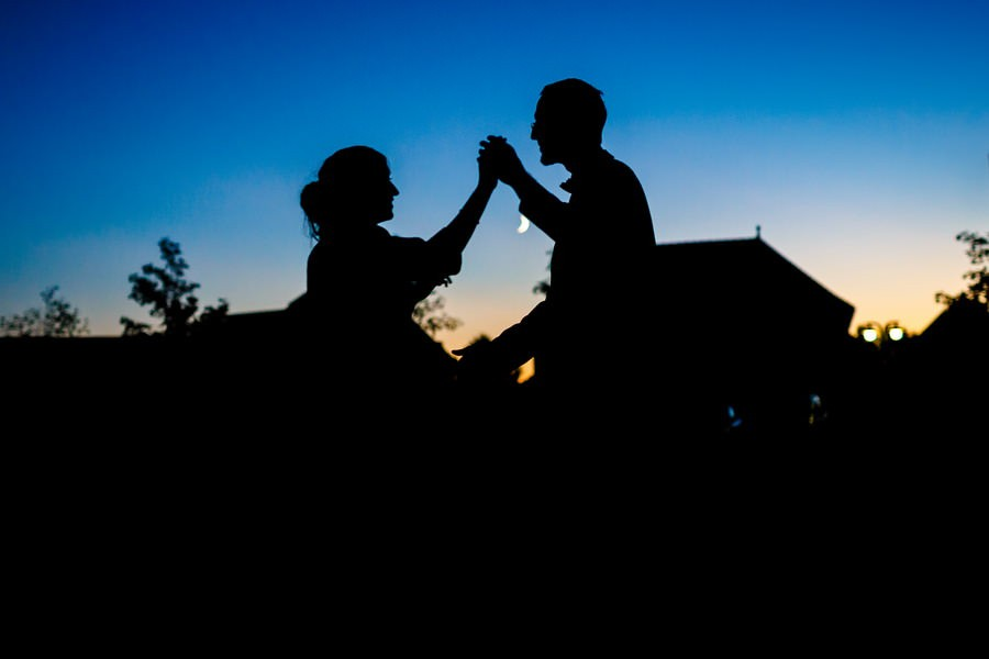 die tanzenden Silhouetten eines Brautpaares vor dunkelblauem Himmel mit Mond