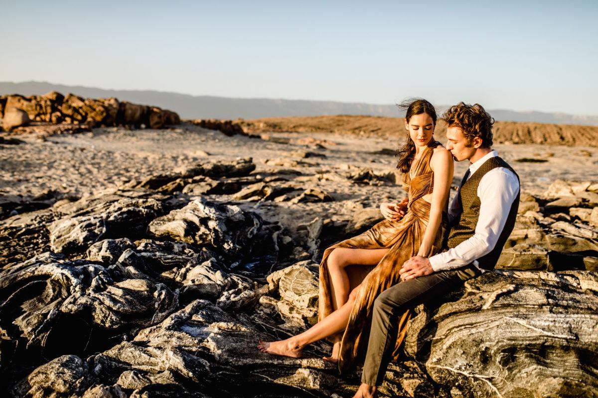 ein junges Paar sitzt auf einem Felsen in der omanischen Wüste