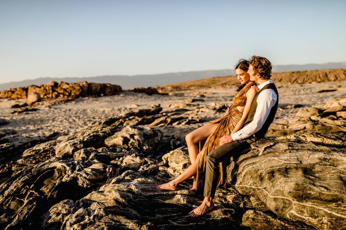 ein junges Paar sitzt auf einem Felsen in der Wüste