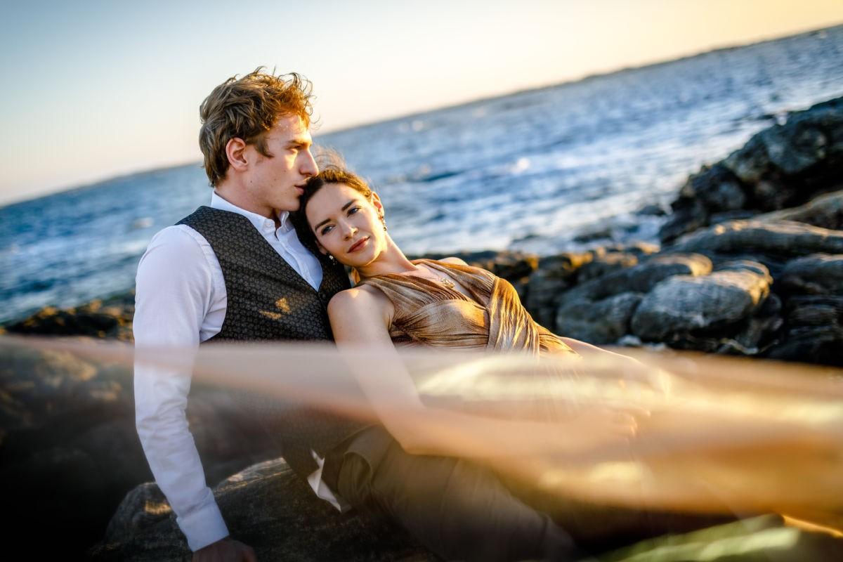 Ein Paar sitzt auf einem Felsen. Im Hintergrund ist das Meer zu sehen. Der Mann küsst das Haar der Frau.