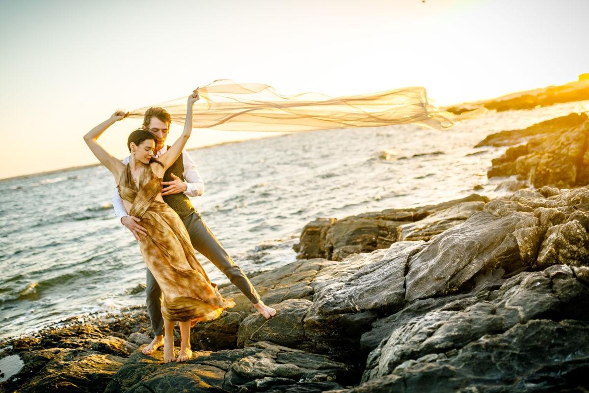 Das Paar steht auf einem Felsen im Meer, ein Tuch über ihren Köpfen weht im Wind