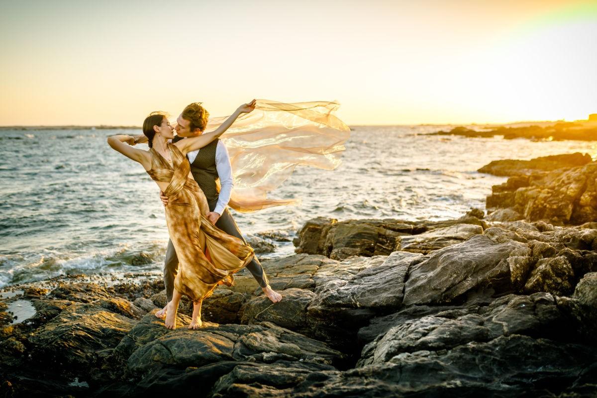 Das Paar steht auf einem Felsen im Meer im Sonnenuntergang