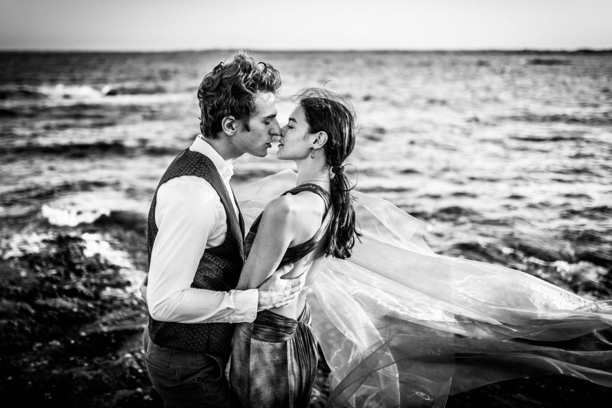 das Paar küsst sich vor der Kulisse des Ozeans, solche Bilder entstehen bei einem Engagementshooting vor der Hochzeit