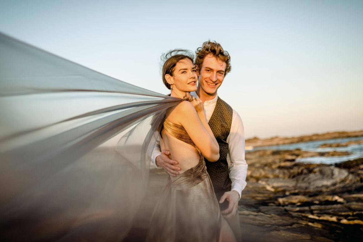 Das Paar steht in einer Felsenlandschaft, ein Tuch weht in die Kamera