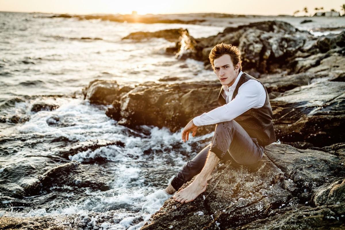 Ein Mann sitzt auf einem Felsen im Meer, Gischt umspielt seine Füße