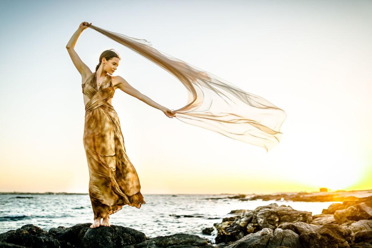 Eine Frau steht mit einem wehenden Tuch in der Hand auf einem Felsen im Meer