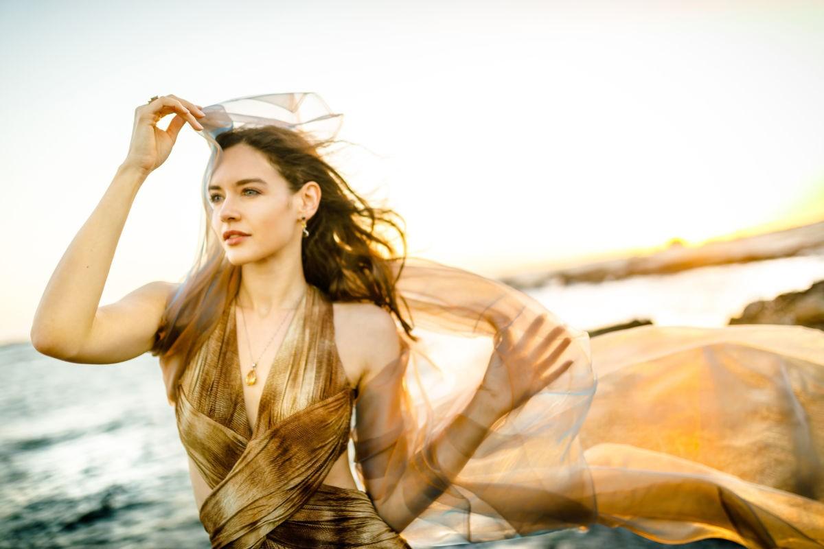 Eine Frau steht mit einem wehenden Tuch in der Hand am Meer und sieht in die Ferne