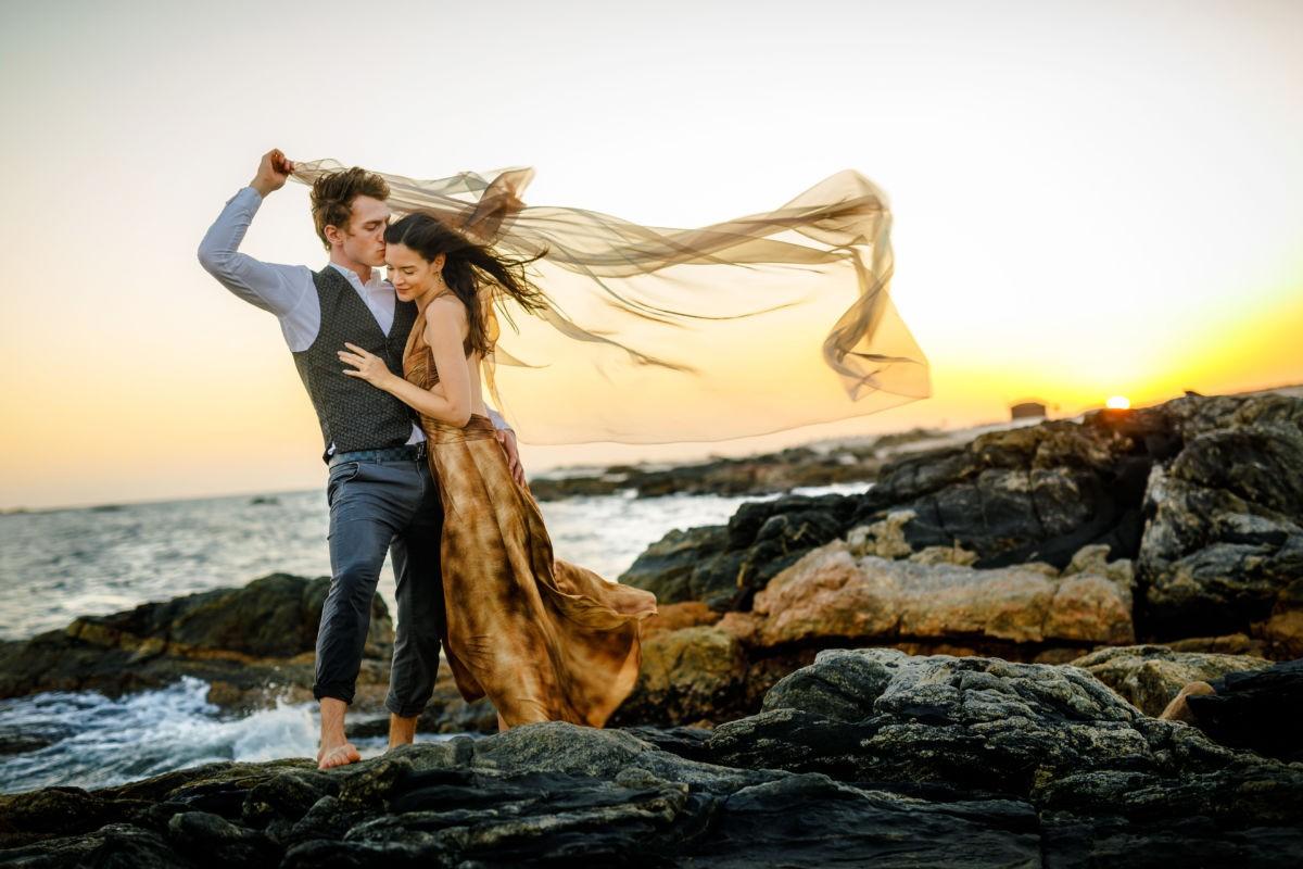bei diesem Verlobungsshooting steht das Paar auf einem Felsen im Meer und liegt sich in den Armen