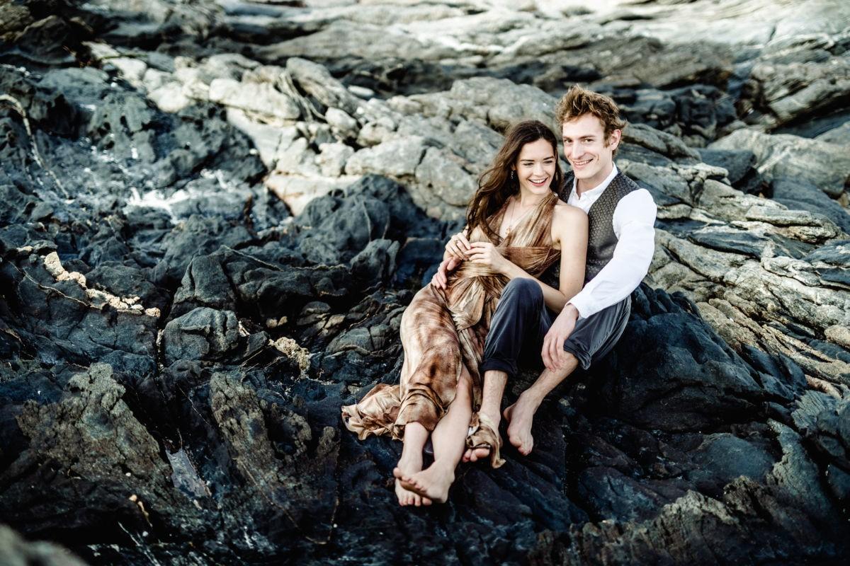 Ein Paar sitzt in einer Felsenlandschaft und lacht