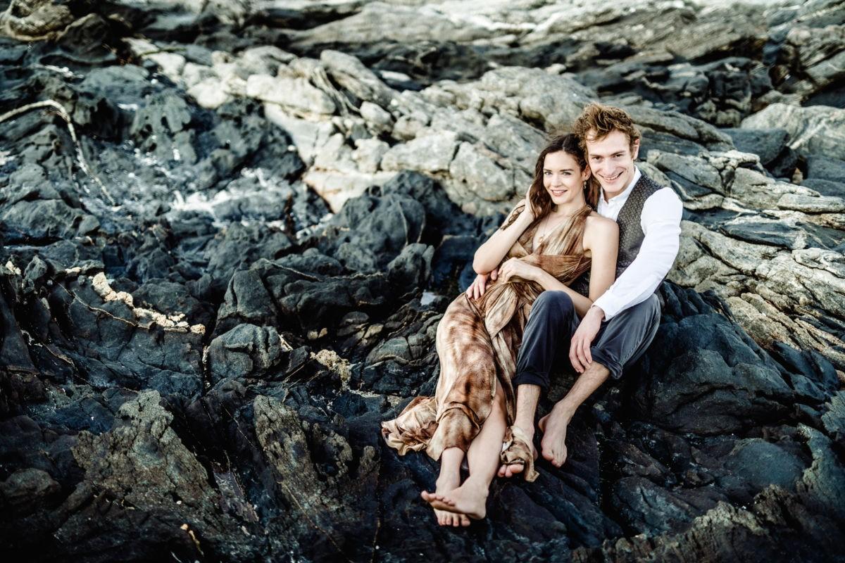 Das Paar sitzt in einer Felsenlandschaft und lächelt in die Kamera