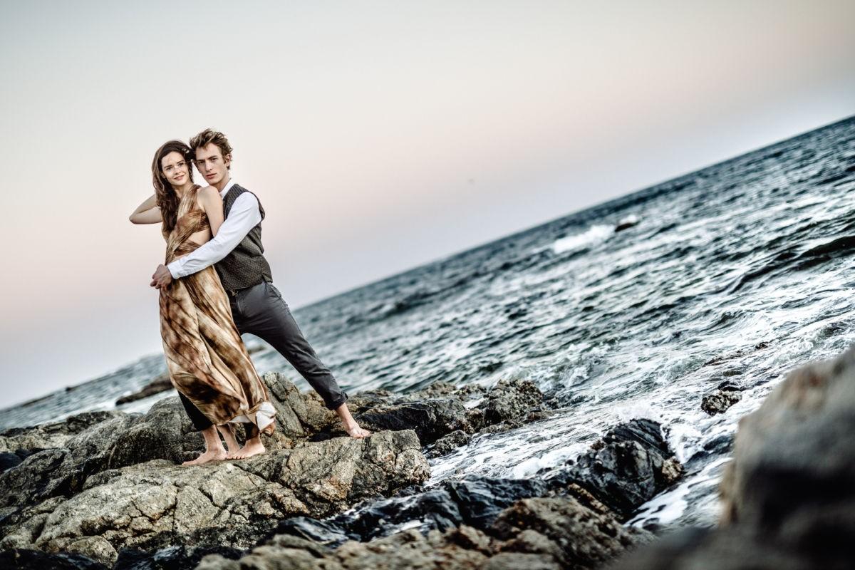 Das Paar steht verschlungen auf einem Felsen im Meer
