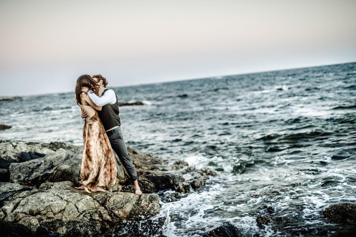 Verlobungsshooting im Oman, das Paar steht auf einer Klippe im Sturm und küsst sich leidenschaftlich