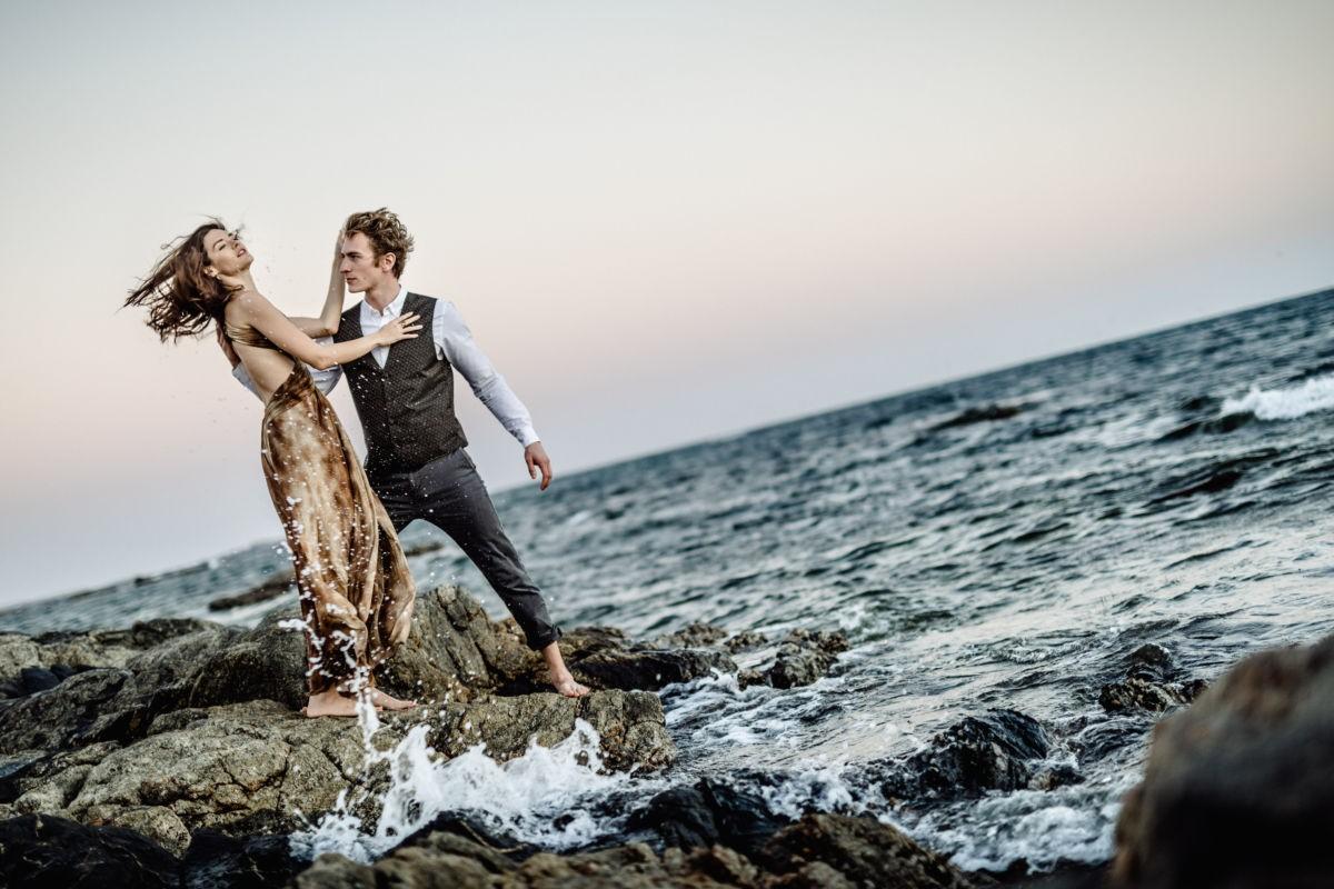 Das Paar steht bei seinem Engagementshooting auf einem Felsen im Meer , Gischt schlägt empor, es ist stürmisch