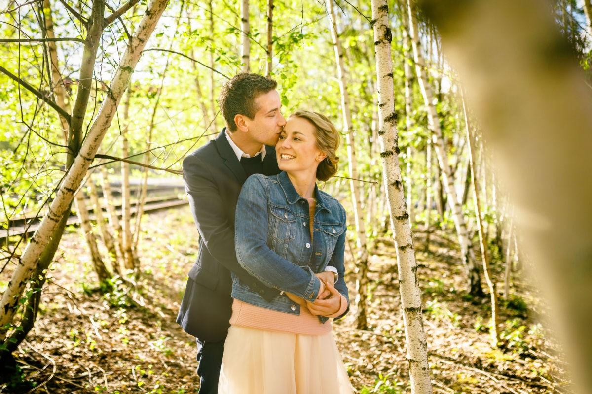 EIn Paar küsst sich Arm in Arm in einem Birkenwald.
