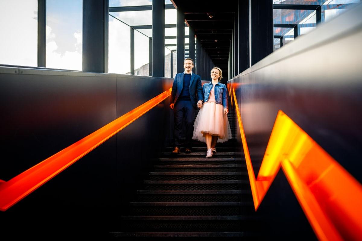 Ein Paar läuft Hand in Hand eine Treppe an der Zeche Zollverein im Ruhrgebiet hinunter.