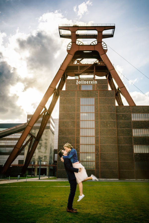Ein Paar küsst sich vor dem großen Förderturm der Zeche Zollverein in Essen