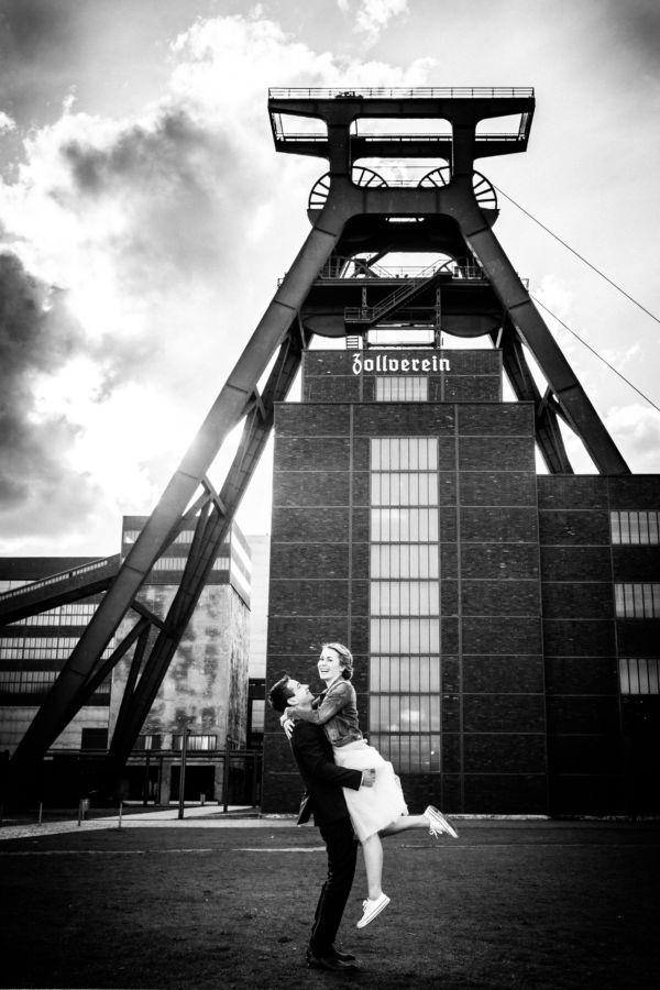 Ein Paar wirbelt verliebt vor dem großen Förderturm der Zeche Zollverein in Essen herum und lacht.