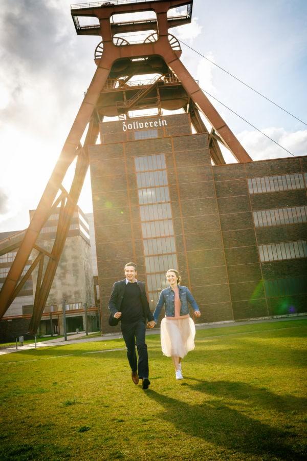 Ein Paar läuft Hand in Hand vor dem Förderturm der Zeche Zollverein in Essen auf die Kamera zu und lacht.