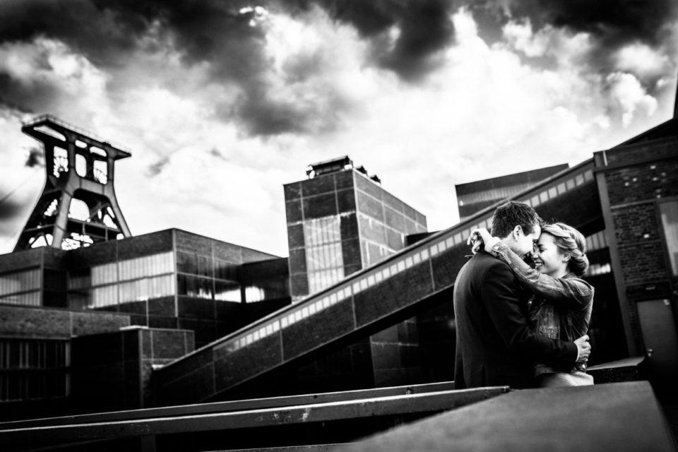 Ein Paar umarmt sich. Im Hintergrund sind die Industriebauten der eche Zollverein in Essen im Ruhrgebiet zu sehen.