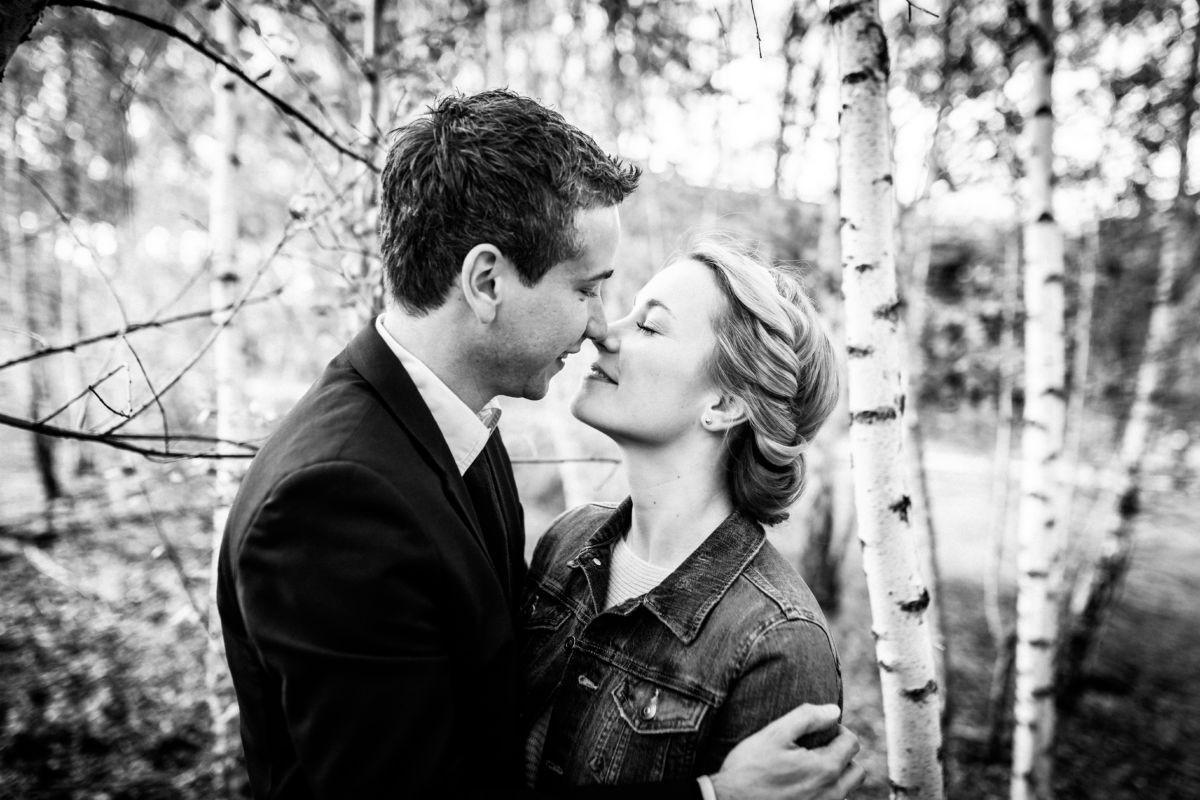Ein Paar küsst sich in einem Wald.