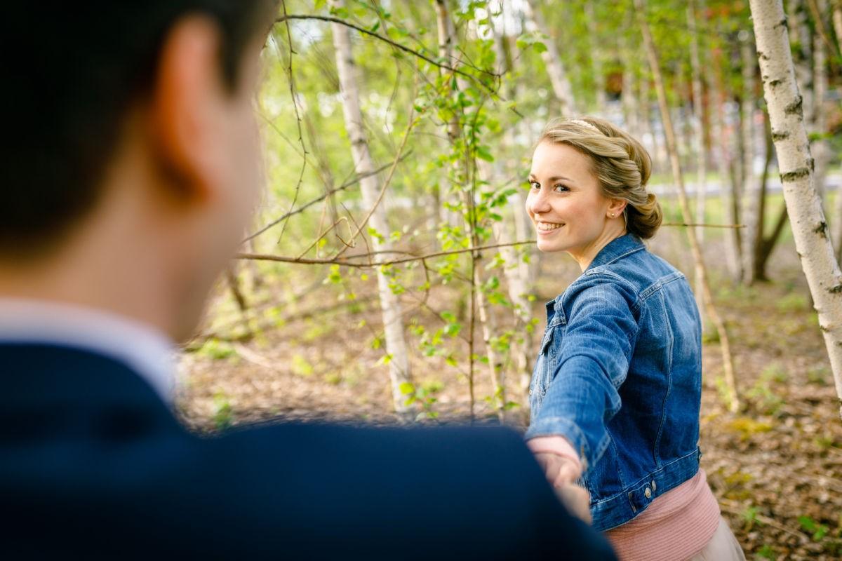 Eine junge Frau strahlt ihren Mann an und hält seine Hand.