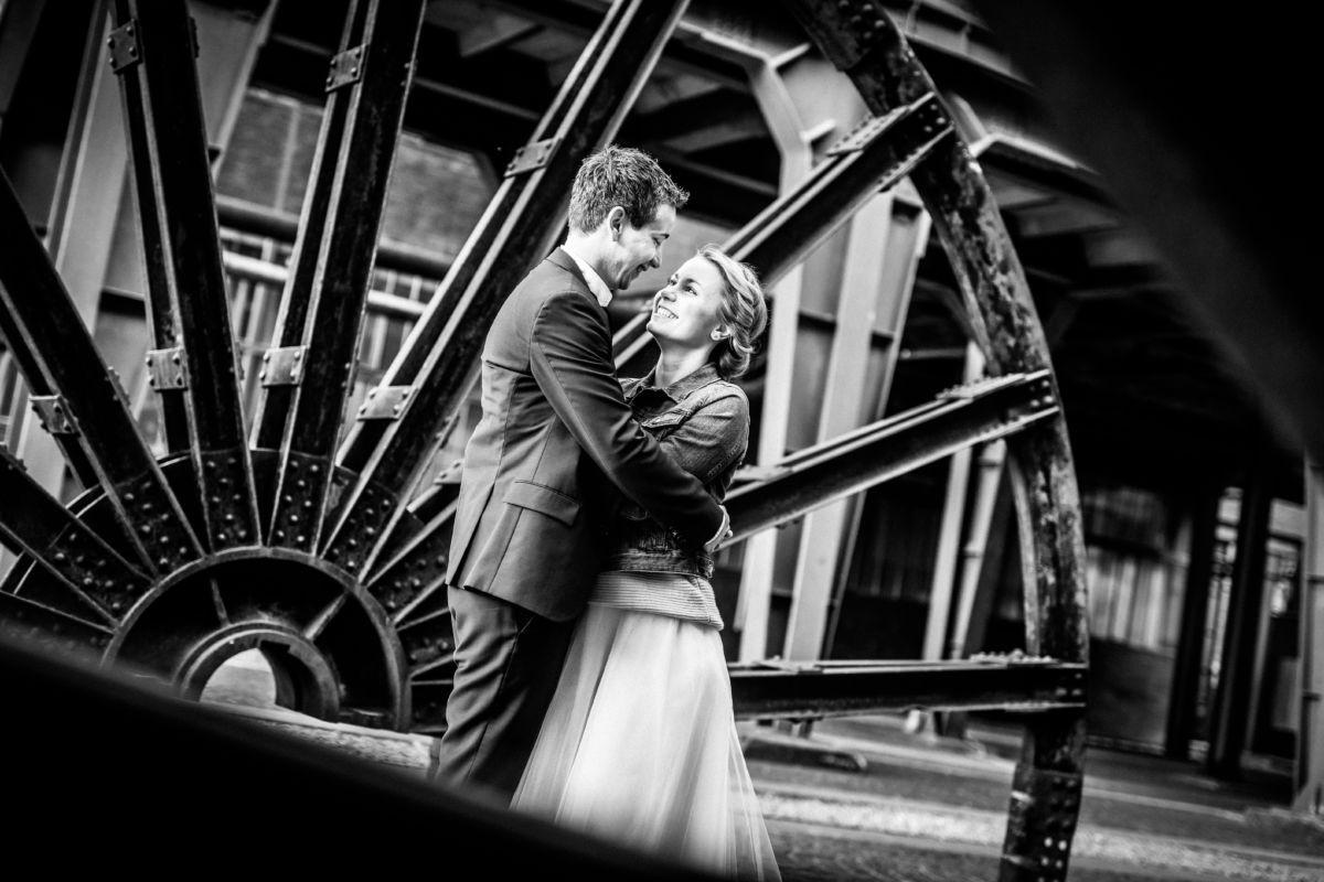Ein Paar sieht sich verliebt in die Augen vor einem alten Zechenrad auf dem Grundstück der Zeche Zollverein in Essen, Ruhrgebiet.