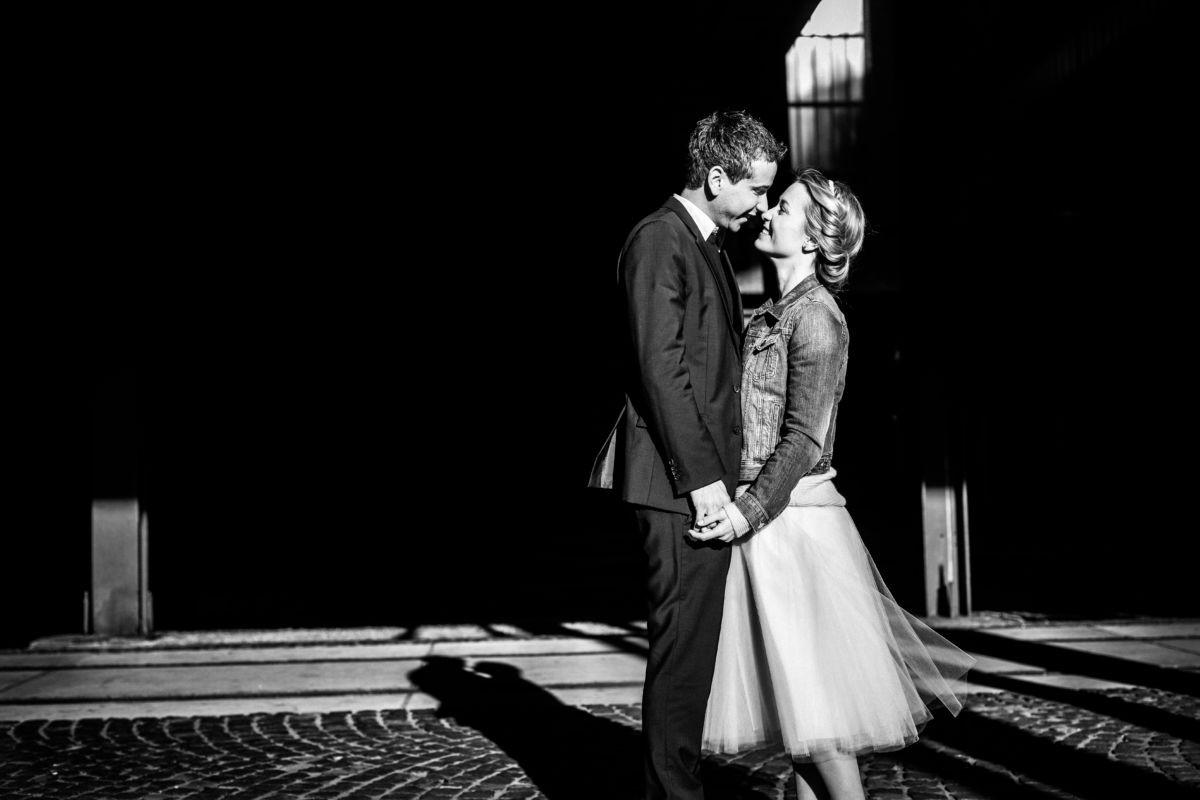 Ein Paar sieht sich verliebt in die Augen, ihr Schatten ist gut sichtbar auf dem Boden der Zeche Zollverein in Essen zu sehen.