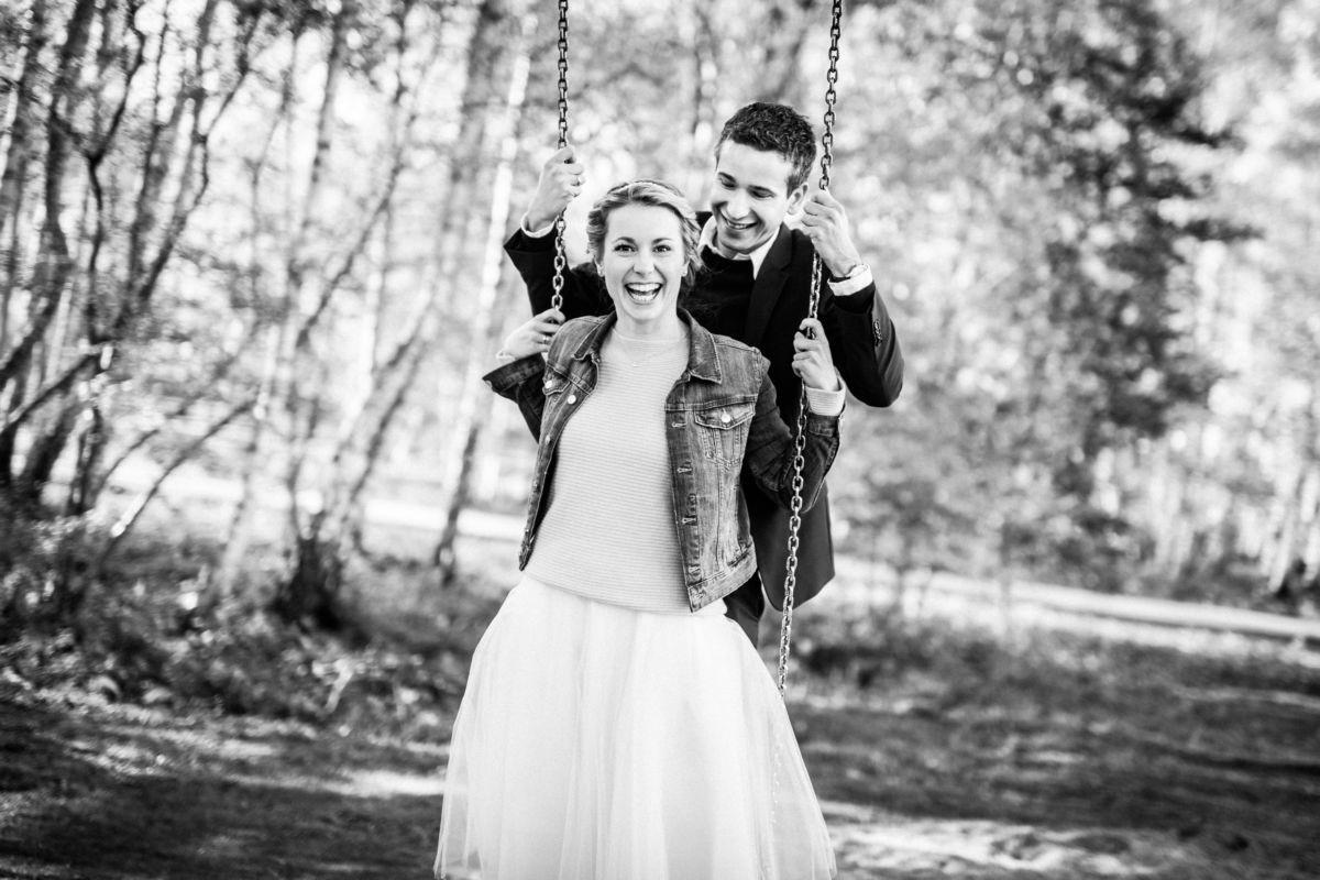 Ein junges Paar steht gemeinsam auf einer Schaukel und lacht auf Zeche Zollverein.