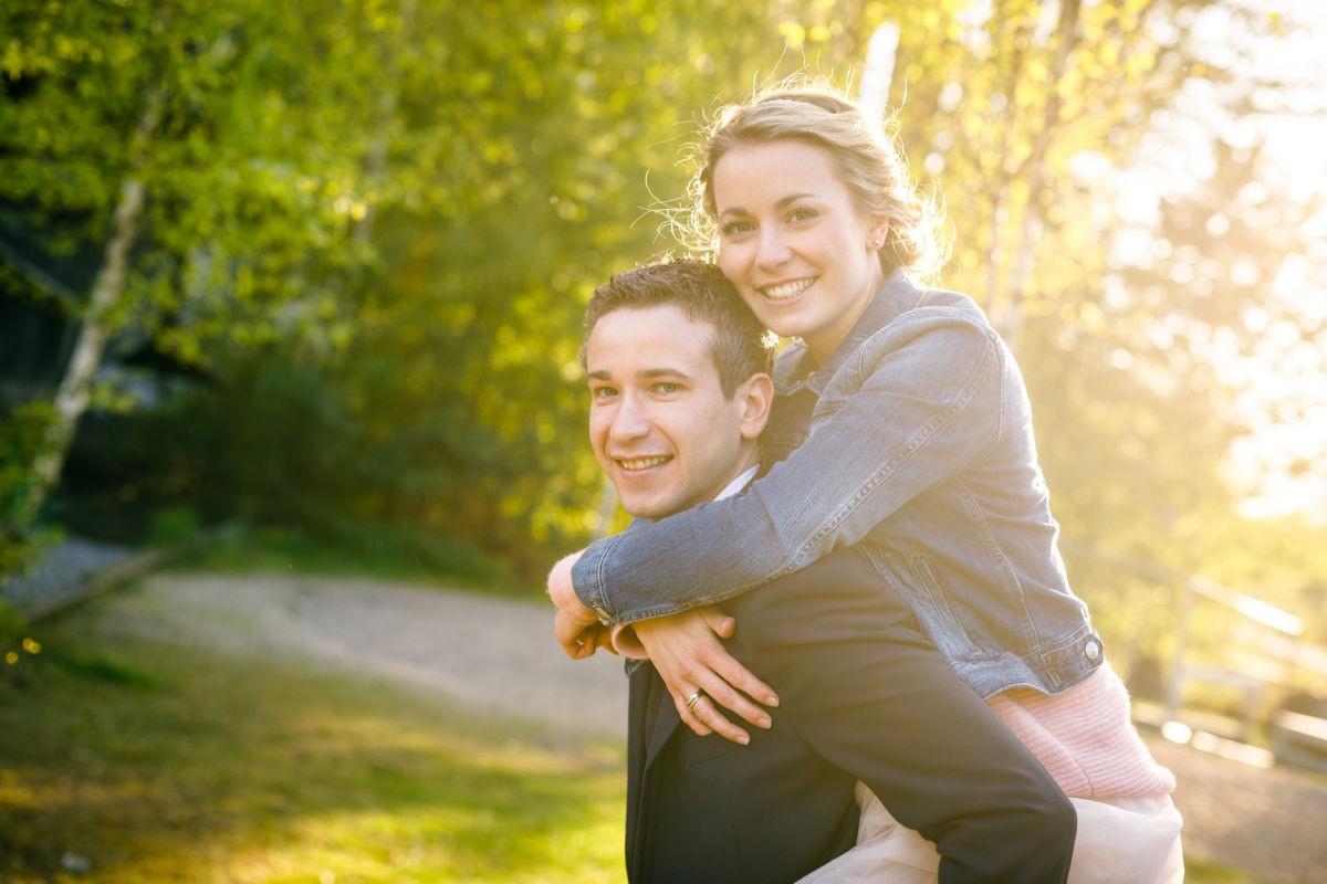Ein junges Paar schau in die Kamera, die Frau sitzt auf dem Rücken des Mannes und umarmt ihn von hinten.