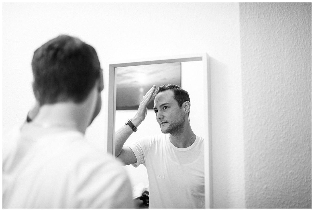 Getting Ready, der Bräutigam stylt sich die Haare.