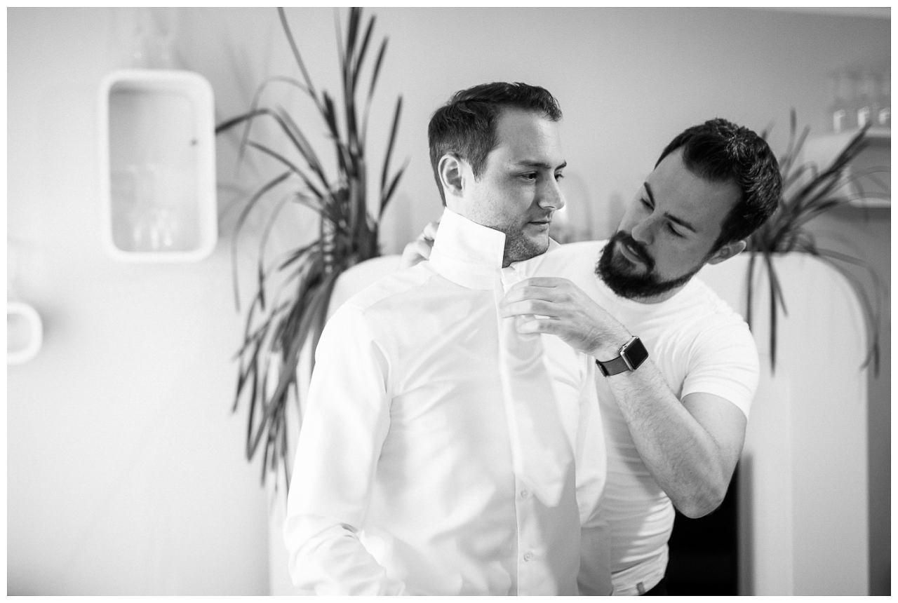 Der Trauzeuge hilft dem Bräutigam beim Getting Ready sich anzukleiden..