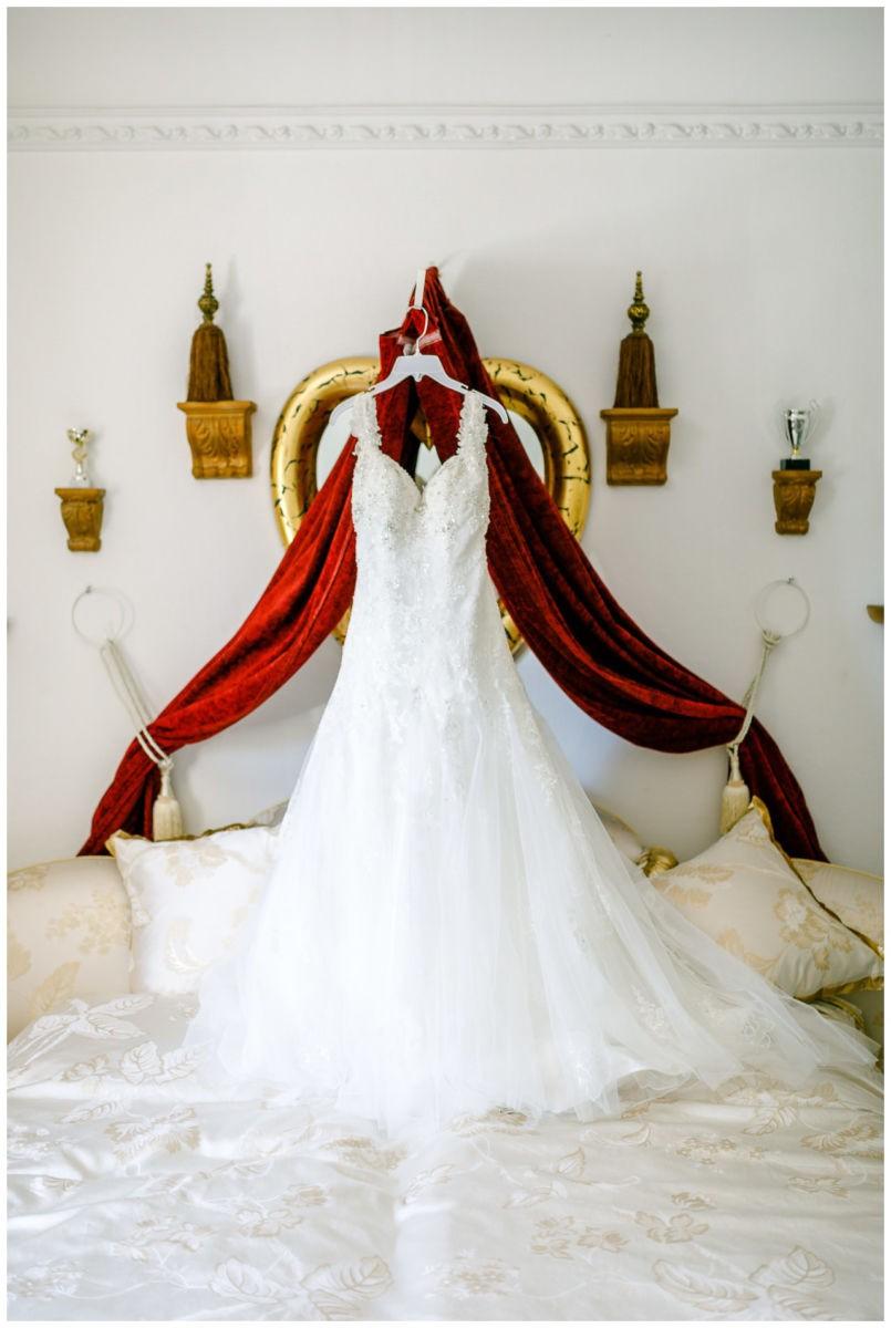 Das Brautkleid hängt über dem Bett im Hotel.