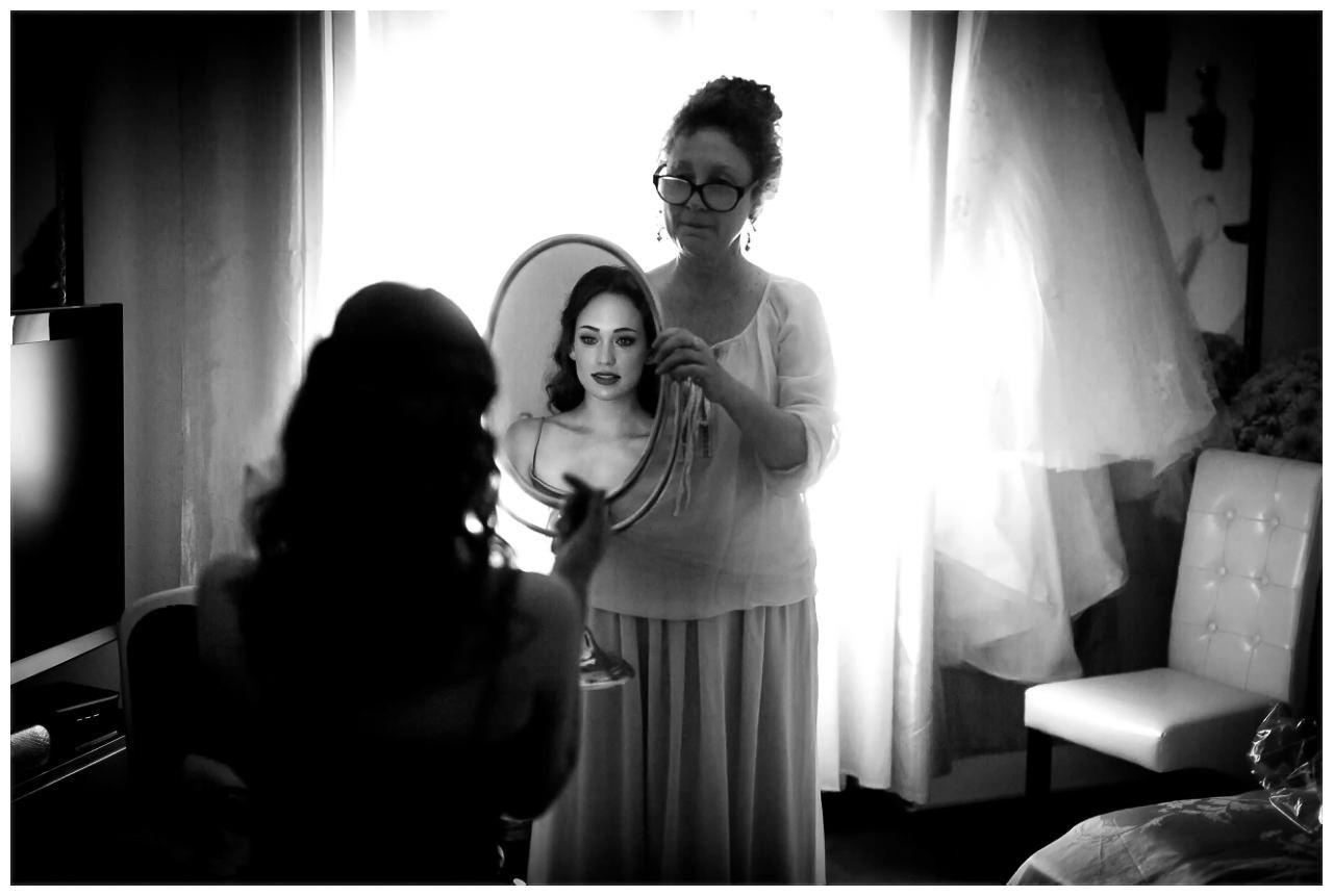 Die Stilistin hält der Braut den Spiegel in der Villa Vera in Wetter.