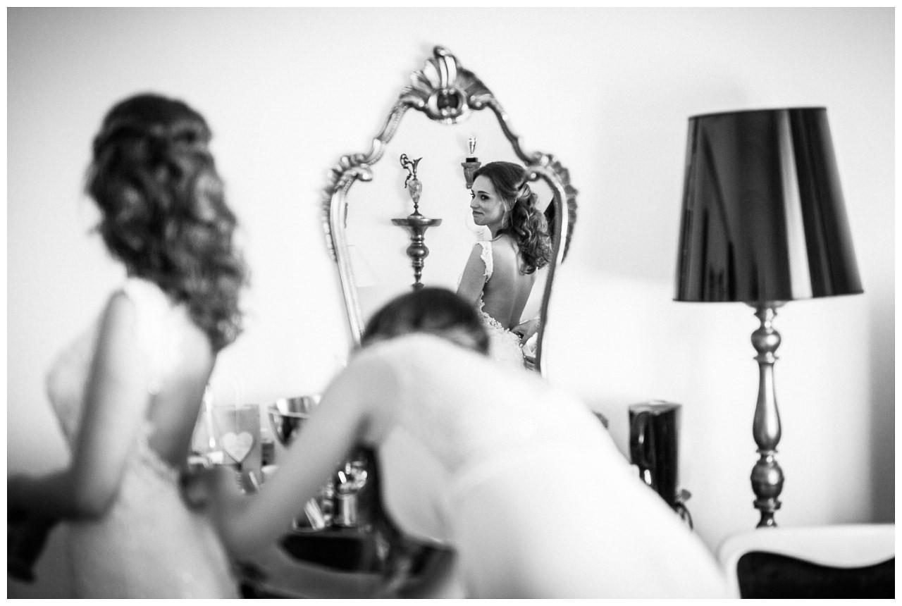 Die Trauzeugin hilft der Braut ihr Brautkleid anzuziehen.