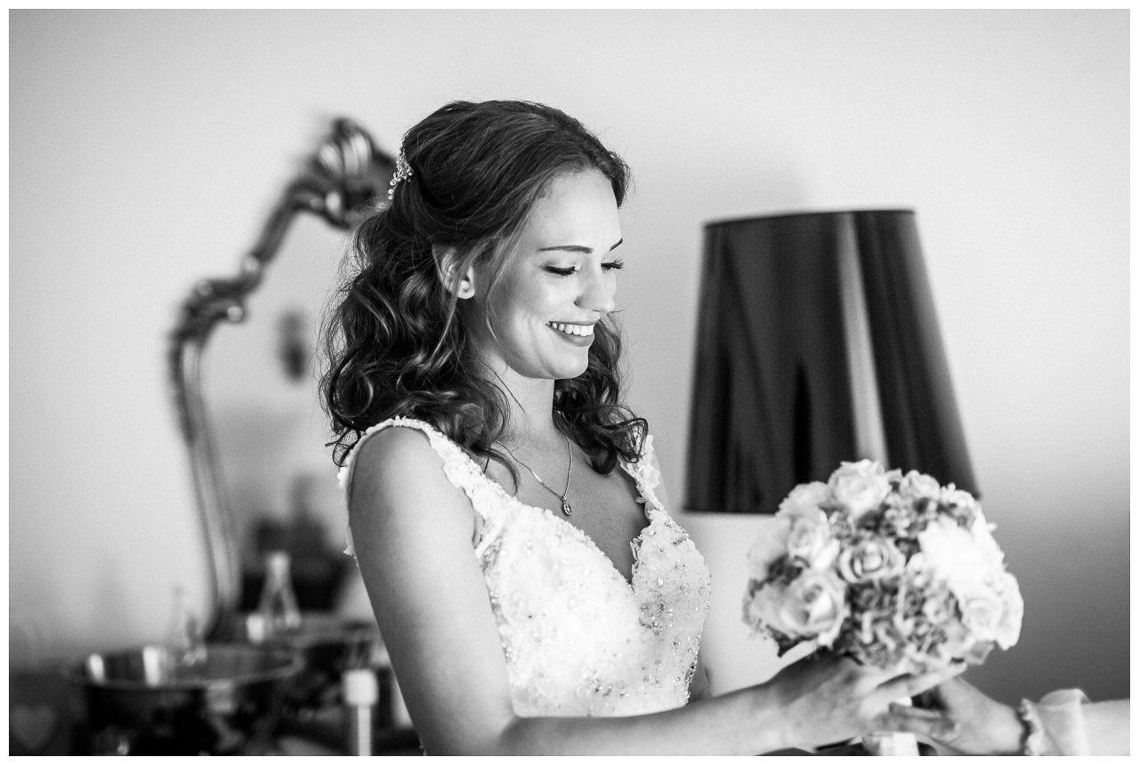 Die Braut sieht ihren Brautstrauß an.
