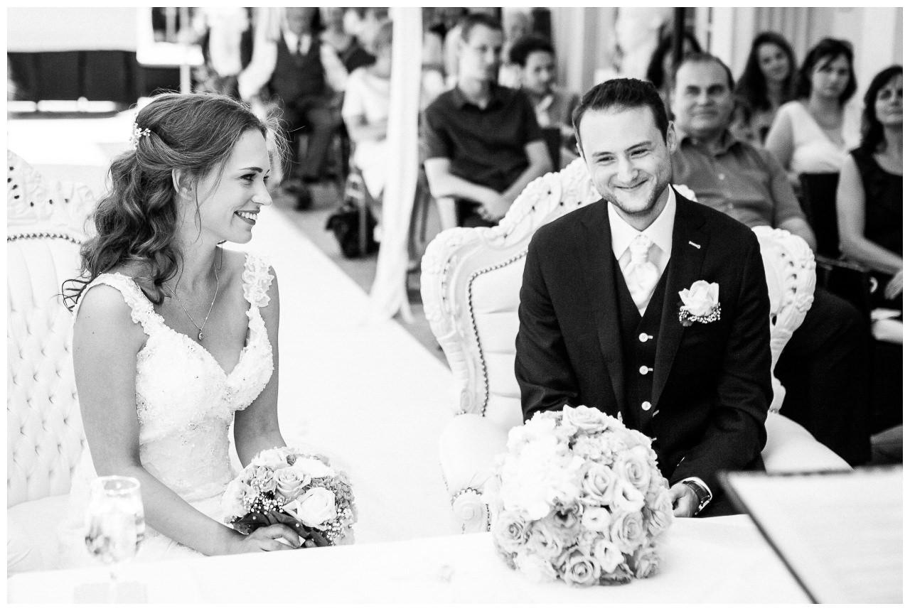 Braut und Bräutigam sitzen vor dem Altar und lächeln sich an.