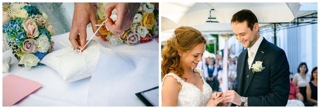 Die Braut steckt dem Bräutigam den Ehering an den Finger.