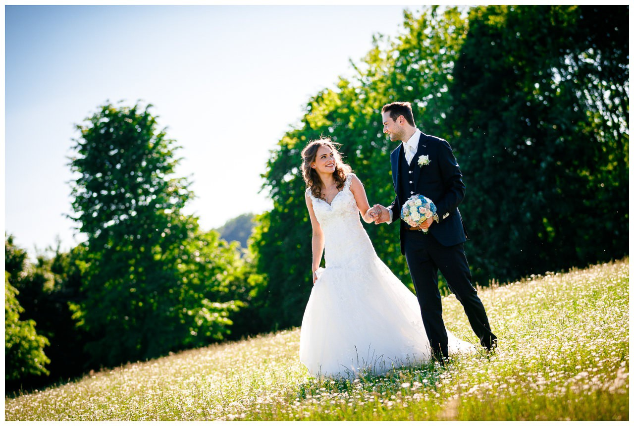Paarshooting Hochzeit, das Brautpaar läuft Hand in Hand auf einer Wiese.