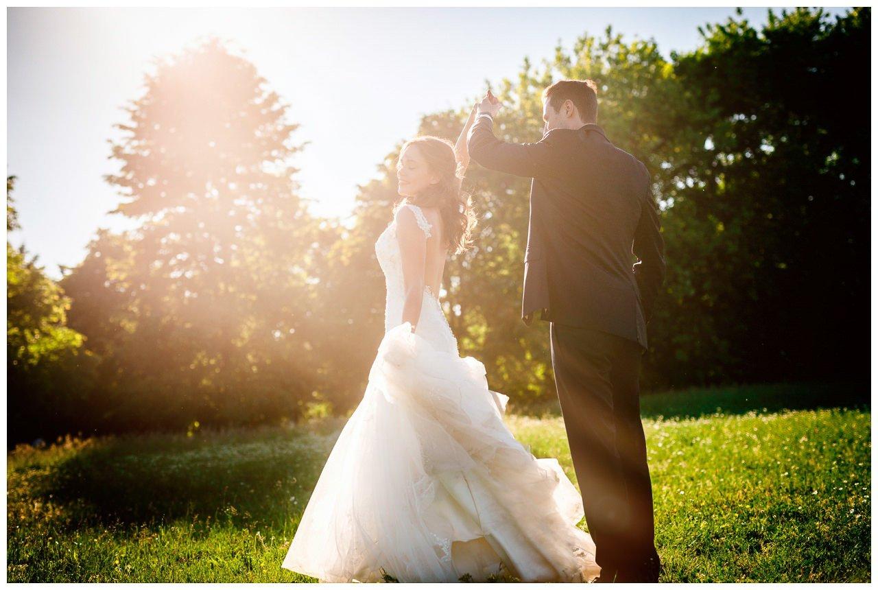 Das Brautpaar tanzt beim Brautshooting auf einer Wiese in der Natur.