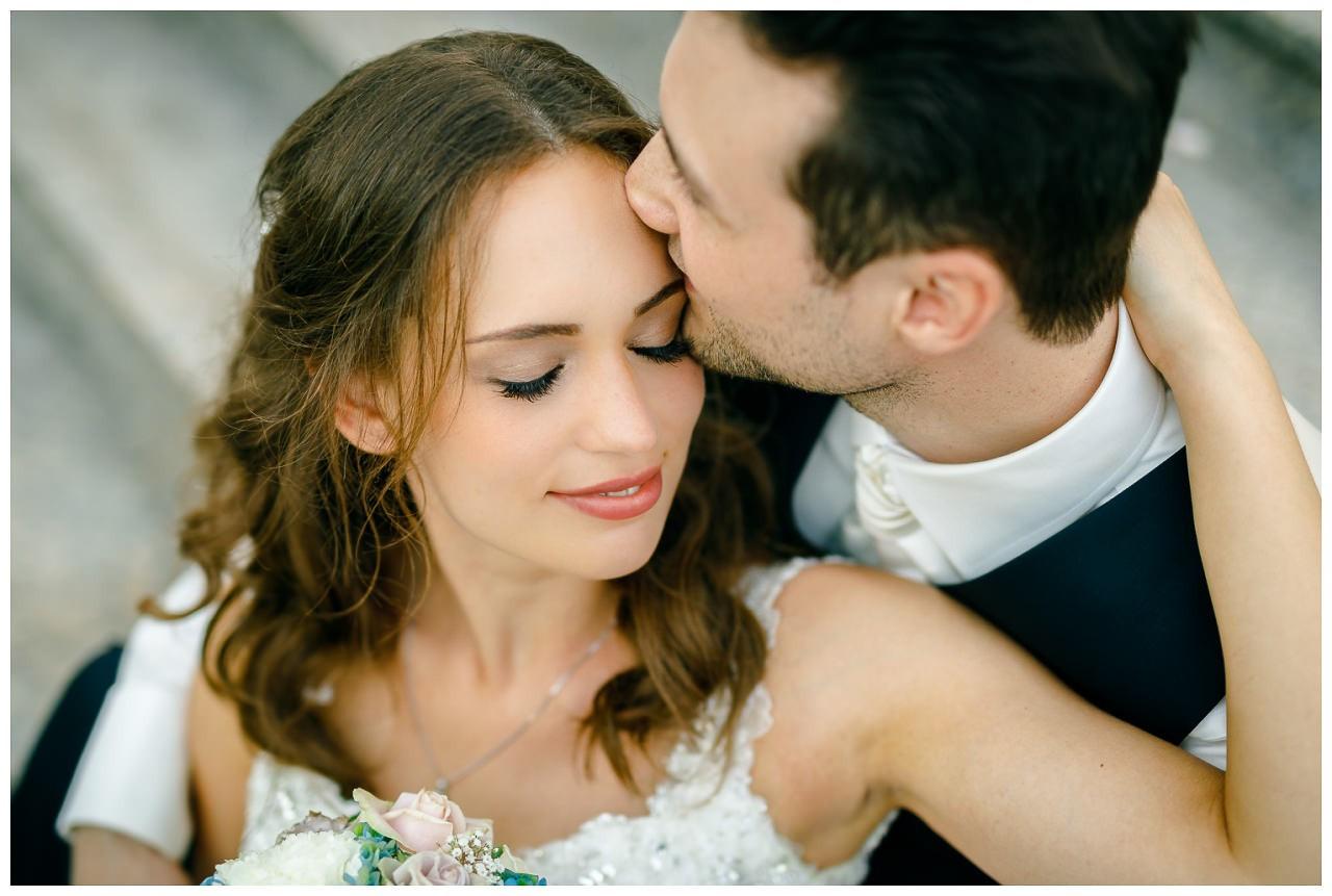 Der Bräutigam gibt der Braut einen Kuss auf die Stirn.